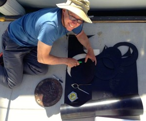Cutting diesel impervious nitrile into inspection plate gaskets for Kandu's fuel tanks at the Silver Gate Yacht Club guest dock.